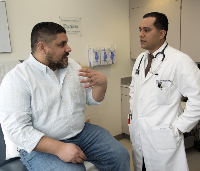 Rafael Garcia-Cortes, MD, (right) speaks with a patient.
